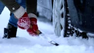 Close up of woman shoveling snow from car video