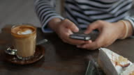 Close up of woman using smartphone at coffee shop , 4k(UHD) video