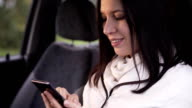 Close up of woman writes a message on a smartphone sitting in the car video