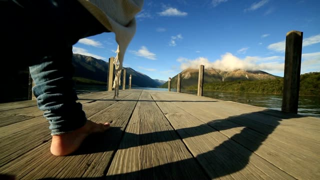 Close up of woman's feet walking on wooden pier above lake video