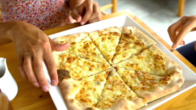 Close up of women taking cheese pizza slices from small plate video