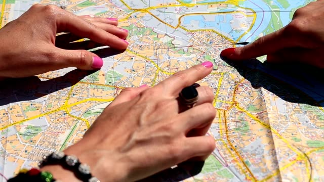 Close up of women's arms pointing map with fingers video