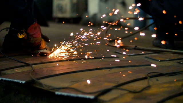 Close up of worker hands use angle grinderon metal construction metal. Sparks slowly turns toward the camera. Slow Motion video