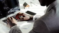 Close up of young black businessman hands typing on laptop computer keyboard in white modern office in the sunny day video