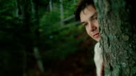 Close up of young carpathian peasant watching someone in the mountain forest and hiding face by the tree video