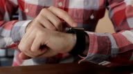 Close up of young man using smartwatch while sitting in cafe video