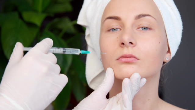 Close up of young woman having a botox injection at beauty salon video