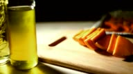 Close up olive oil bottle on table. Healthy food. Pumpkin pieces video