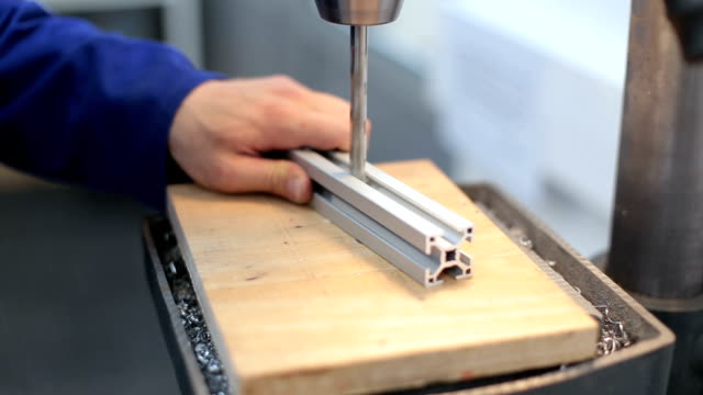Close up on an worker drilling in an workshop video