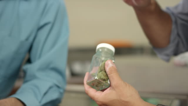 Close up on the hands of an associate at a marijuana shop holding a product video