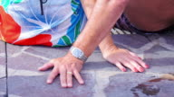 Close up on the hands of an older couple sitting by a pool video