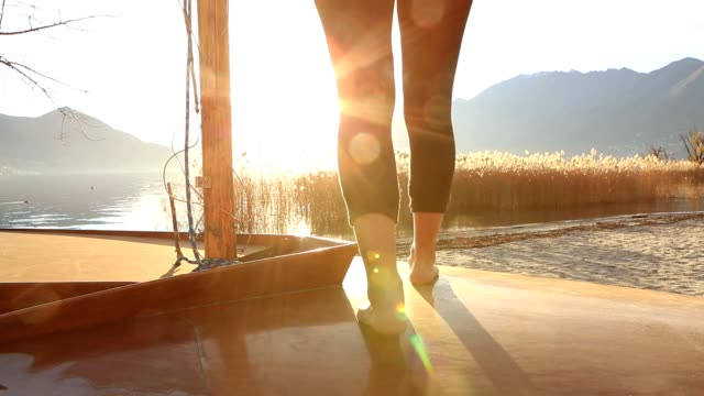 Close up on woman's feet standing on boat above lake video