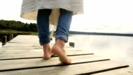Close up on woman's feet standing on jetty above lake video