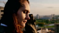 close up portrait of a girl standing on the roof girl straightens her hair, looking at the city. Slow motion video