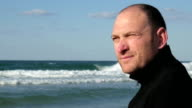 Close up portrait of a serious forty years man on backdrop of the Mediterranean Sea video