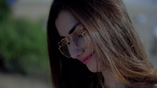 Close up portrait of beautiful young caucasian woman in transparent sunglasses smiling at camera. Slow motion video