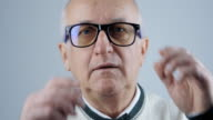 close up portrait of senior man with glasses and gray hair video
