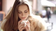 Close up portrait of smart girl drinks a cup of steaming coffee. FullHD video