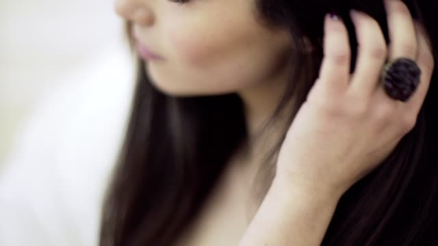 Close up portrait of young beautiful woman touching her brown hair video