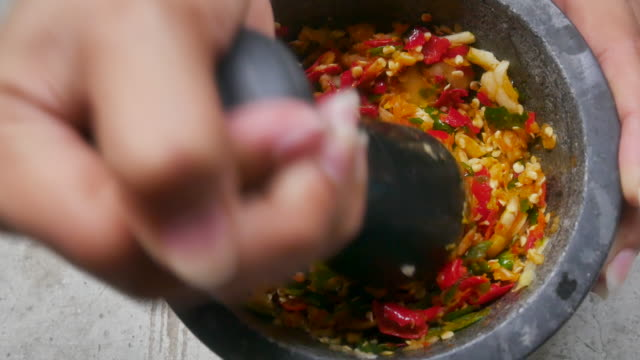 Close up pounding fresh herbs in a mortar with a pestle video