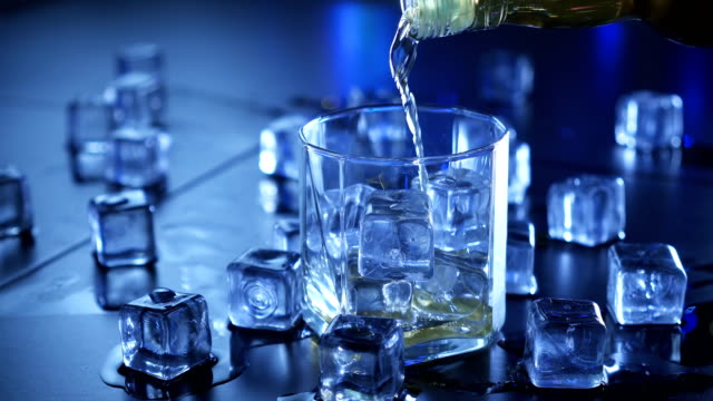 Close up pouring whiskey to glass over ice cubes. video