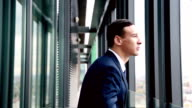 Close up profile of smiling businessman standing by window with city view video