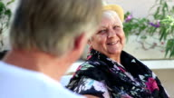 Close up senior woman laughing as her husband talks to her video