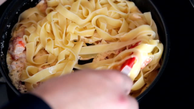 Close up shooting of man hands cooking pasta in pan on stove video