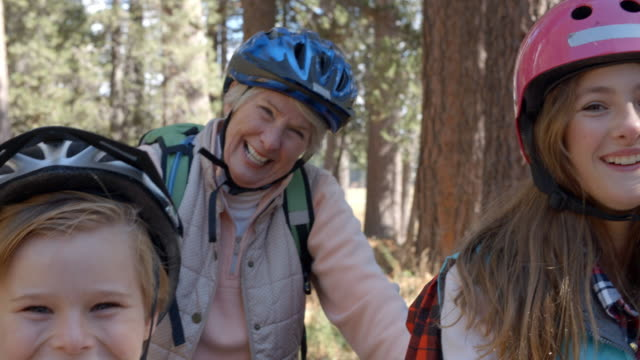 Close up shot, children and grandparents on bikes in forest video