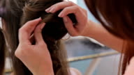 Close up shot. Hairdresser doing hairstyle for young pretty woman - top knot video