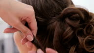 Close up shot. Hairdresser finishing hairstyle for young pretty woman video