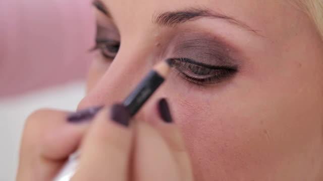 Close up shot. Make-up artist applying eyeliner around the entire eye of model video