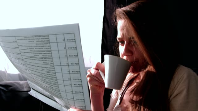 Close up shot of a beautiful young woman reading or studying and drinking tea in the living room video