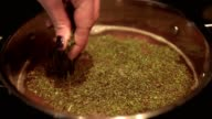 Close up shot of a female hand adding spices herbs to a meal in a cooking pot on the hot plate video