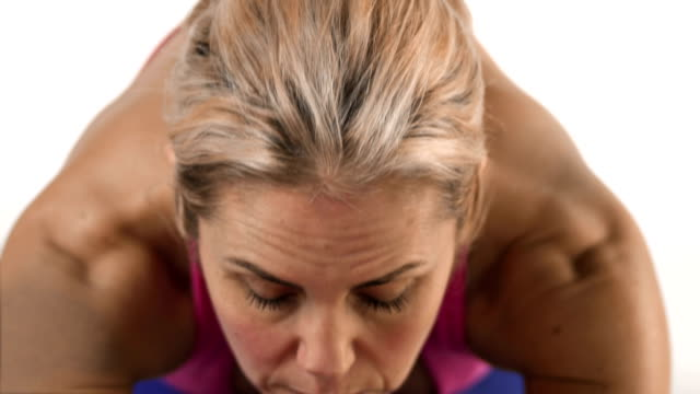 Close up shot of a focused white female doing yoga poses video