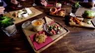 Close up shot of a wooden table with vegetarian snacks that are beautifully decorated and served by the waiter. Different vegetables lie in plates, sauces in bowls video