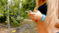 Close up shot of a working out girl who is using her smart phone outdoors video