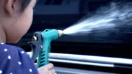 Close up shot of child hand holding water hose and inject to wash a car video