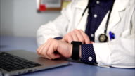 Close up shot of doctor wearing smart watch on his hand working in his cabinet. video