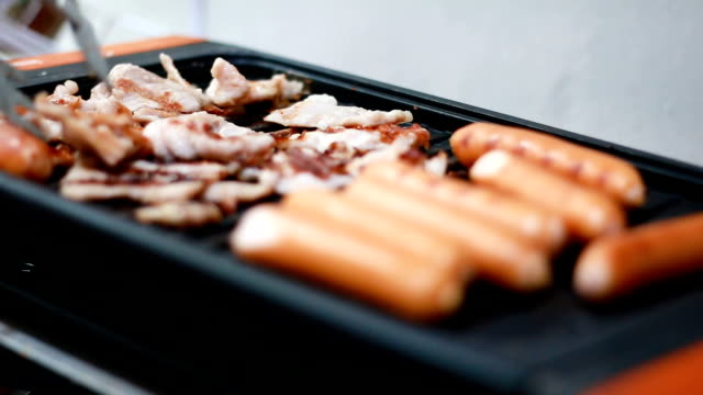 Close up shot of grilling  sausage on electric hob with ambient sound and shallow depth of field video