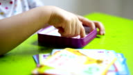 Close up shot of little girl's hands lifting and placing cards video