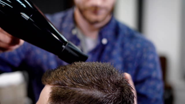 close up shot of the head of a man who came to barbershop, the hairdresser dries the client's head with the help of warm air from the hair dryer video