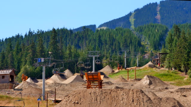 Close Up Shot of Whistler Bike Park Jumps, Gondola Cable Car and Mountains video