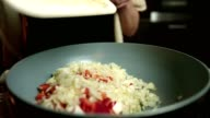 Close up slow motion shot of hands adding chopped onion and red pepper to a meal cooking in frying pan video