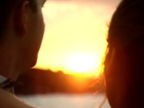 Close up, soft focus of two lovers faces in sunset video