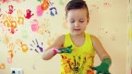 Close up veiw of cute little boy with painted hands after leaving his colorful handprints on the wall and showing his thumb up. Young happy family. Mother and child concept video