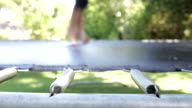 Close Up View Of Feet Bouncing On Trampoline In Garden video