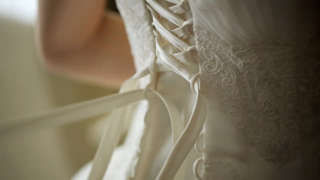 Close up view of woman tighten corset of wedding dress video