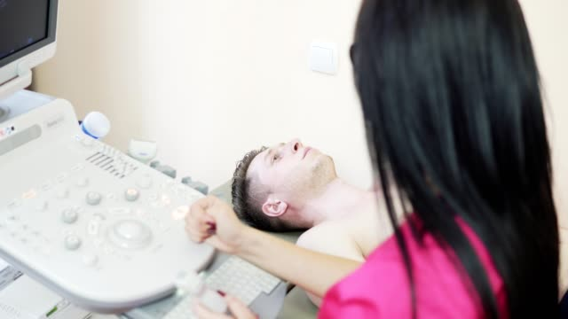 Close up view of young female doctor with long hair in rose uniform is screaning her patient's heart with ultrasonography, looking at the screen, and consulting. video
