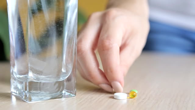 Close up view of young woman holding ginseng vitamins and minerals pills video